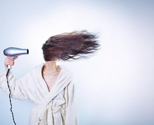 Frau föhnt Schuppen aus den Haaren